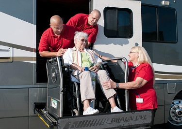 staff-with-patient-boarding-coach